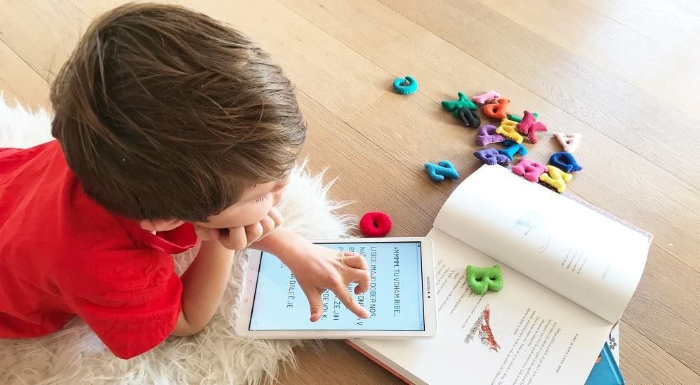 Kobi_Kid reading on the floor with book and tablet